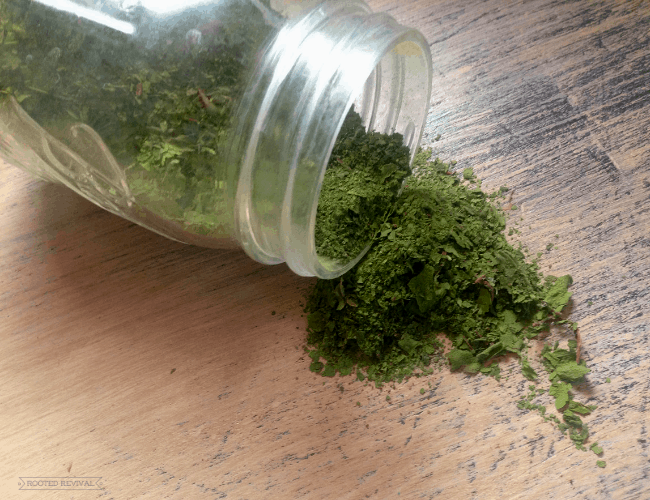 Mason jar tipped on side with green powder spilling out