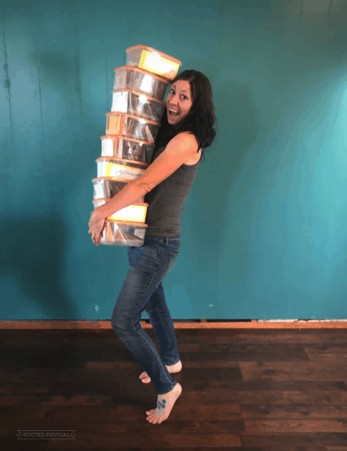 Woman holding lots of storage containers and smiling