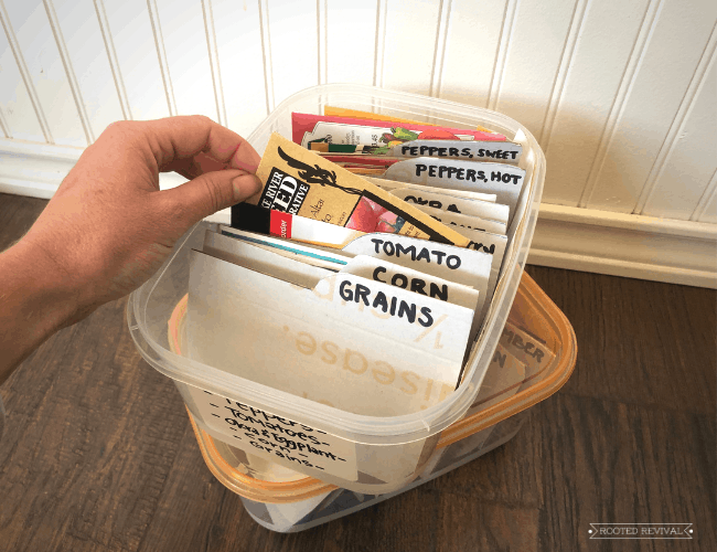 Hand picking up a seed packet out a of a storage bin full of seeds