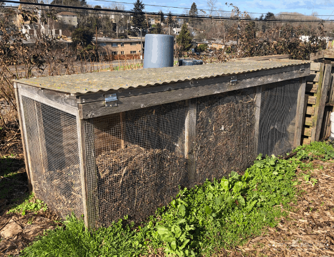 a 3 bin compost system made from wire with metal roofing on top