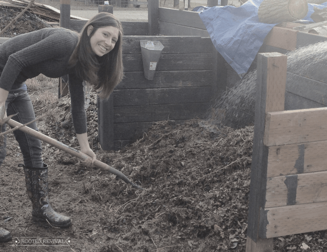 A woman smiling while leaning over to drive a pitchfork into a compost pile
