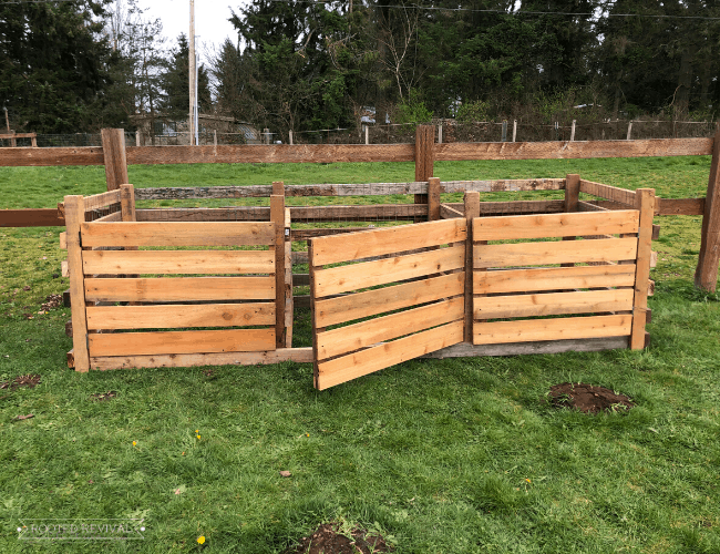 three wooden paneled compost bins. The middle one has the door slightly ajar