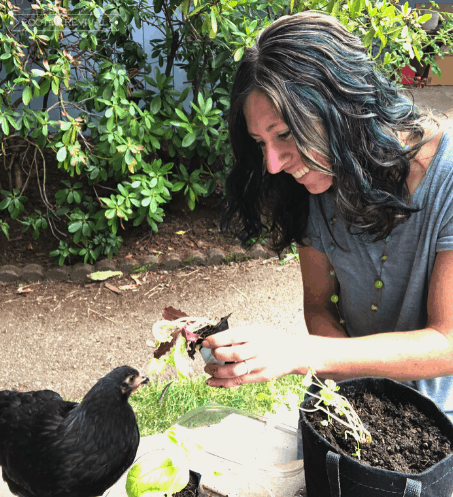 Woman holding seedling up to a black chicken