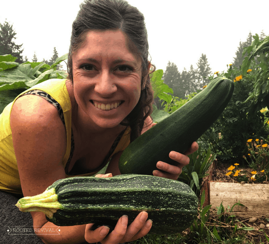 Kaylee holding up two large zucchini squash. She is smiling and wearing a yellow tank top.
